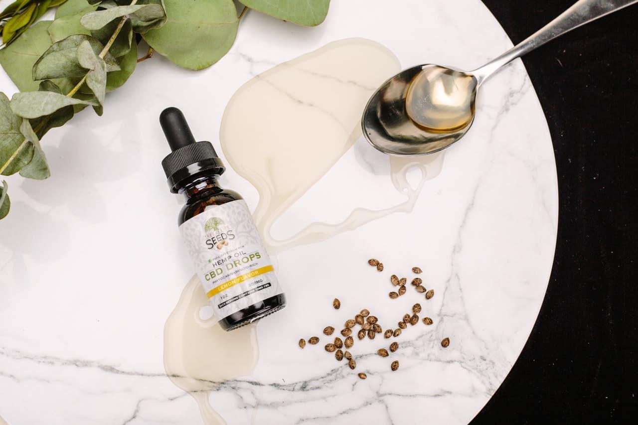bottle of cbd drops hemp oil on white table